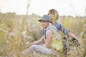 Young couple looking away while relaxing in field