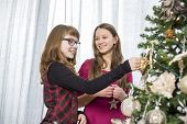 Sisters decorating on Christmas tree at home