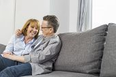 Happy loving couple sitting on sofa at home