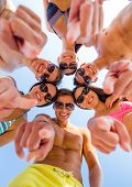 friendship, summer vacation, gesture and people concept - group of smiling friends wearing swimwear