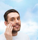 health and beauty concept - beautiful smiling man touching his face or applying cream