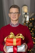 Portrait of mature man holding stack of Christmas presents