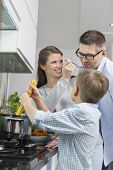 Happy family preparing spaghetti in kitchen