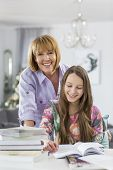 Portrait of happy mother assisting daughter in doing homework at table