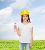 childhood, construction and people concept - smiling little girl in protective helmet with wrench
