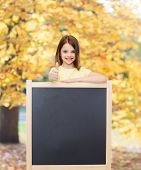 people, advertisement and education concept - happy little girl with blank blackboard showing thumbs