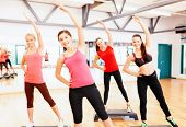 fitness, sport, training, gym and lifestyle concept - group of smiling female doing stretching in gy