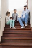 Father sitting with children on steps at home