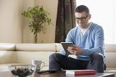 Smiling man using tablet PC at home