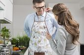 Woman helping man to put on apron in kitchen