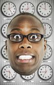 Man with Glasses standing in front of clocks