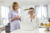 Mature couple using laptop at home