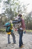 Rear view of hiking couple with backpacks walking in forest