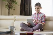 Smiling girl using digital tablet on sofa at home