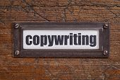 copywriting  - file cabinet label, bronze holder against grunge and scratched wood