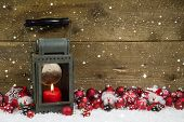 Christmas Latern With Red Candle And Balls On Wooden Background.