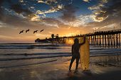 A surfer watches pelicans and the sunset at Oceanside Pier. Oceanside is 40 miles North of San Diego