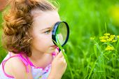 Young girl is looking at flower through magnifier, outdoor shoot