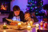Young Father And His Little Boy Reading Book By A Fireplace On Christmas