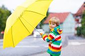 Adorable Toddler Child With Yellow Umbrella And Colorful Jacket Outdoors At Rainy Day