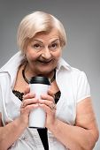Elderly woman holding thermos cup
