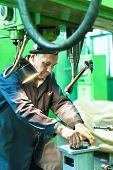 Elderly worker watches on milling machine work