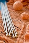 Many Wooden Spokes Lie On An Orange Knitted Plaid
