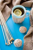 A Cup Of Tea With Lemon, Beige Knitted Blanket And Spokes Lie On Blue Tray