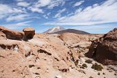 Volcanic rock and Ollague volcano in Atacama desert