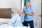 Portrait of senior man being assisted by male caretaker in bedroom at nursing home