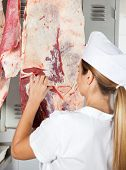 Rear view of female butcher analyzing raw meat hanging in shop