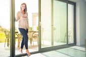 Young cheerful pregnant woman entering house from garden
