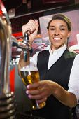 Pretty barmaid pulling pint of beer in a bar