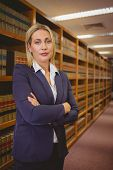 Serious woman standing with arms crossed in library