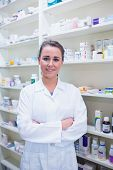 Portrait of a smiling student in lab coat with arms crossed in the pharmacy
