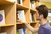 University student choosing books on bookshelves in the bookcase at the university