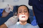 Dentist and nurse examining a scared patient in dental clinic