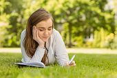 University student lying and writing on notepad in park at school