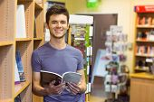 Smiling university student holding textbook in the bookcase at the university