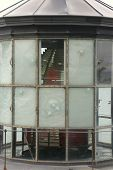 picture of mear  - Glass panes that have been shot out or damaged revealing the fresnel lens at the historic Cape Meares lighthouse in Oregon.