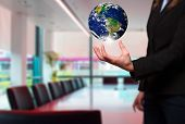 Businesswoman is holding out a Globe. Office background