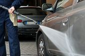stock photo of pressure-wash  - Closeup Of A Mechanic Washing A Car By Pressured Water At Garage - JPG