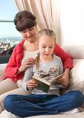 Senior lady with her granddaughter relax together on the the and reading the book
