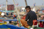 Fisherman sits at the fishing boat, Al Hudaydah, Yemen.