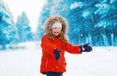 Cheerful Child Having Fun Outdoors With Snowball In Winter Snowy Day