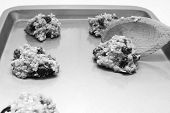 stock photo of baked raisin cookies  - Using a wooden spoon to place oatmeal raisin cookie dough onto a baking sheet  - JPG