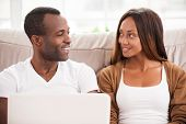 pic of heterosexual couple  - Beautiful young African couple sitting on the couch and looking at each other while using laptop together - JPG