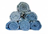 picture of denim jeans  - roll blue denim jeans arranged in stack on white background - JPG