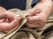 Closeup of senior woman's hands basting linen border using pins