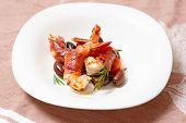 Shrimps with bacon, olives and rosemary in white plate